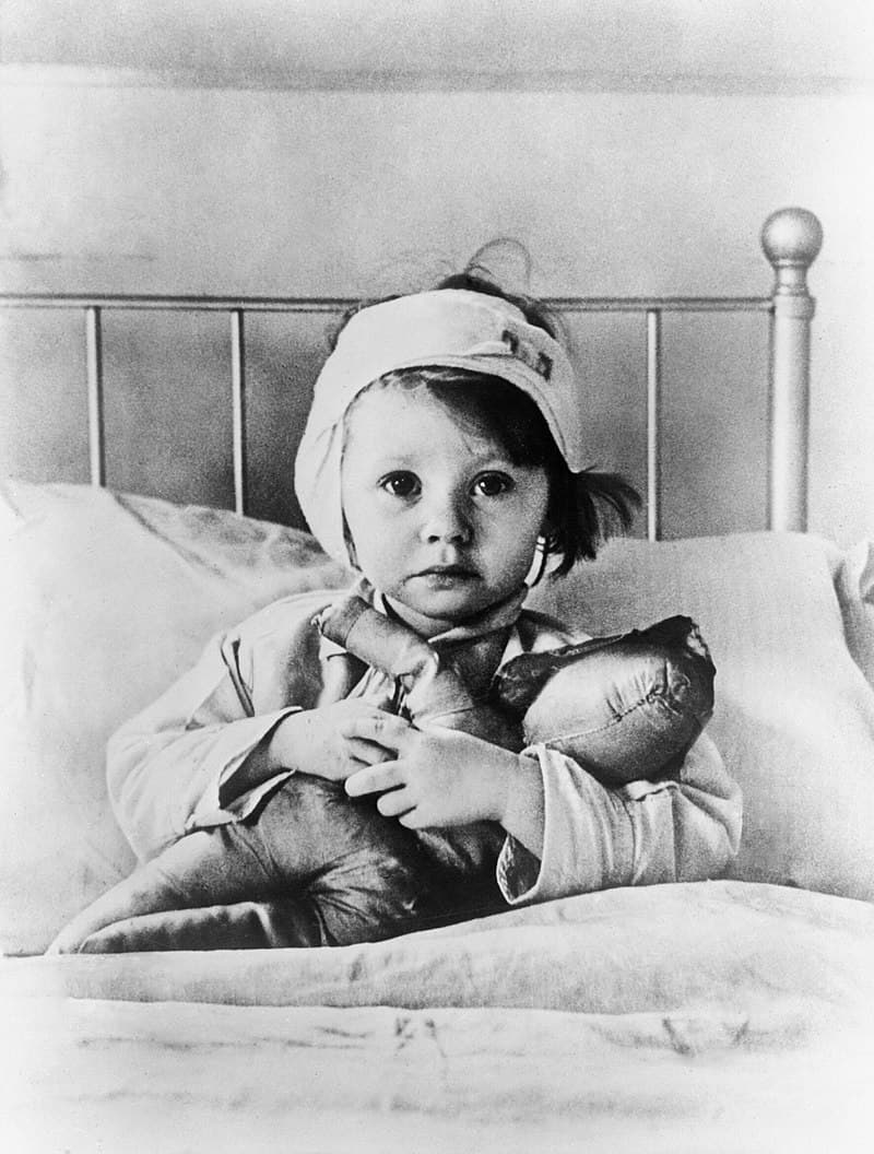 History Story: #8 Eileen Dunne, aged three, sits in bed with her doll at Great Ormond Street Hospital for Sick Children, after being injured during an air raid on London in September 1940