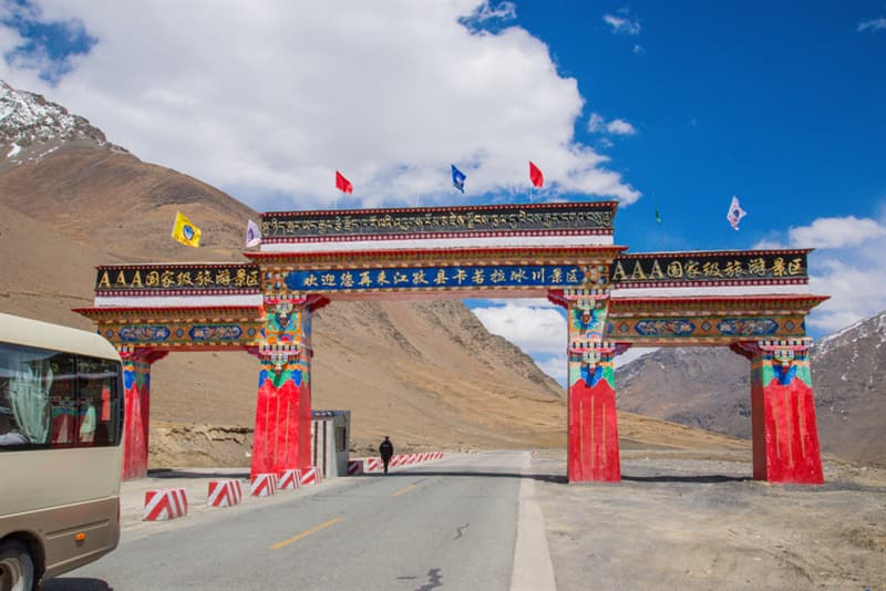Geography Story: #12 The mountain pass with traditional gate in Central Tibet near Lhasa under the blue sky