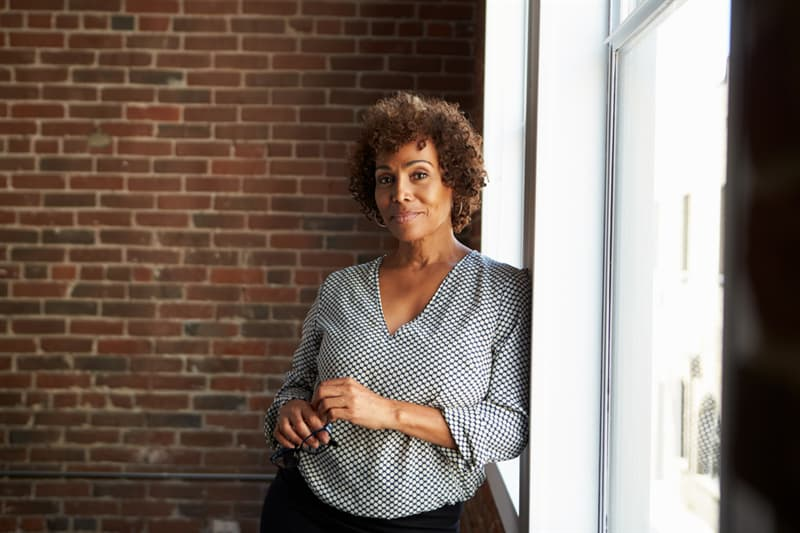 age Story: Maintain good posture african american woman standing at the window trivia free quiz personality test anti aging how to look younger look younger