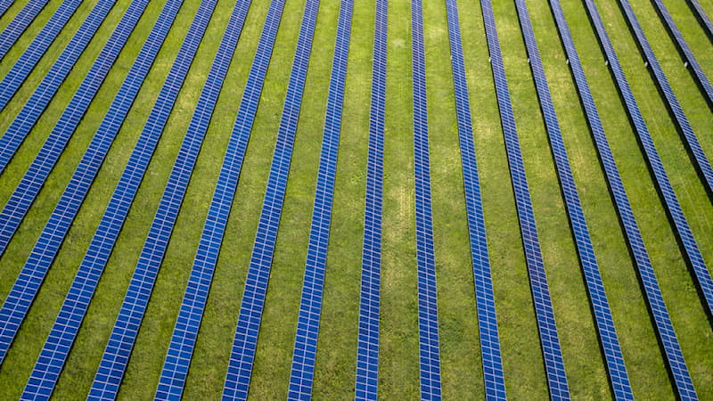 Geography Story: #9 Aerial drone shot of multiple solar panels on a vast green field.
