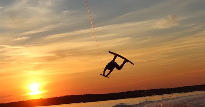 Sport Trivia Question: Which sport includes riding on a short, wide board, surfboarding and performing acrobatic maneuvers?